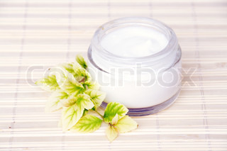 Cosmetic Face Cream Bottle and Yellow Leaves