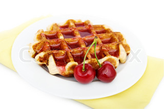 Waffles with cherryes on a white plate