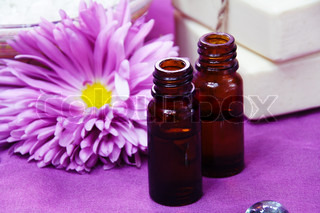 Aroma Oil Bottles with Flower and Soap Background