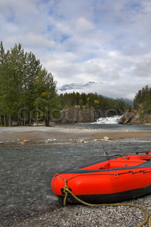 Red boats of a kayak on coast of the mountain river in Canada