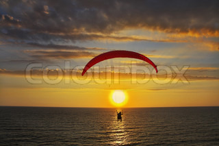 Operated parachute above the sea on a sunset