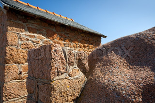 wall of traditional stone Breton house made from granite rock