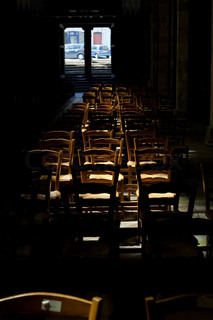 wood chairs under sunbeam in cathedral (