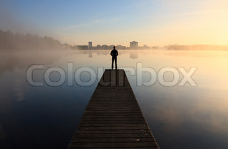 Man looking at foggy sunrise over a lake.