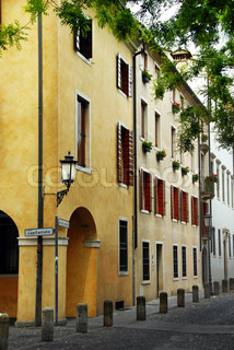 corner of yellow building with street light on piazza Capitaniato in Padua, Italy