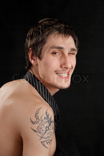 naked, unshaven young man with a sly look on a black background