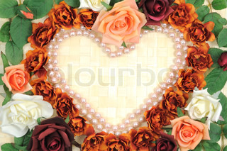 Batch of colorful roses in heart shape on a wooden background