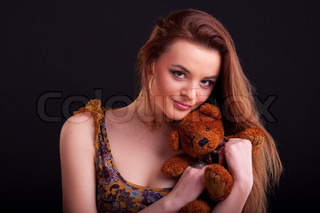 Beautiful longhair girl is holding the teddy bear