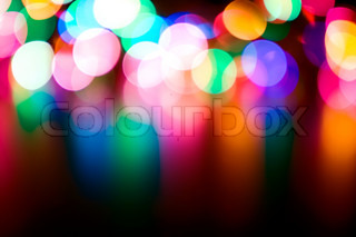 Defocused colorful flashing lights on a black background