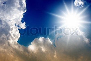 Bright sun and clouds in blue sky