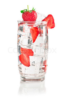 Glass of iced mineral water with ice cubes and strawberry on white surface with reflection