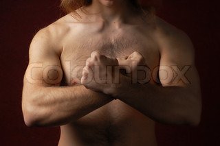 Muscular male torso with crossed arms in a sign of 'X'