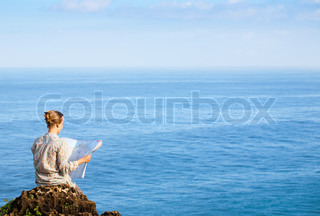 Woman reading map am Meer