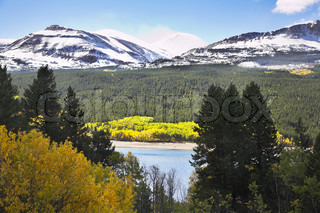Northern landscape - cold lake, snow mountains and yellow bushes