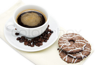 a cup of coffee and biscuits on beige cloth