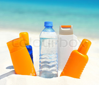 water and sun protection cream on beach background
