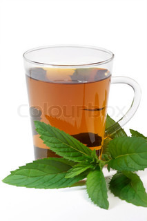 Herbal tea in a teaglass with peppermint leaves on white background