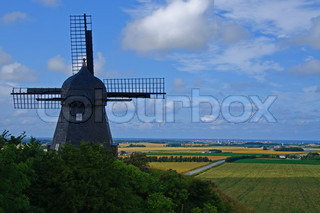 An old dark windmill on a  hill with a view over fields and to the ocean