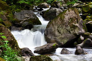 A cool stream of water and rocks in the mountains. Unspoiled nature.