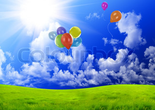 Color balloons in the dark blue sky over a green glade