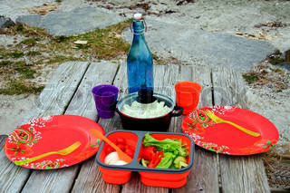 A picnic table with paper plates and salad