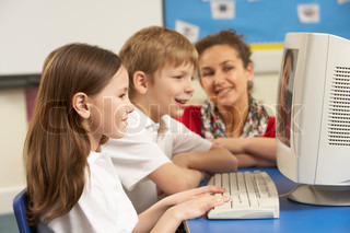 Schoolchildren In IT Class Using Computer with teacher