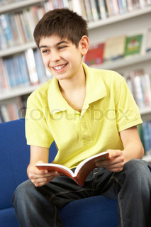 Male Teenage Student In Library Reading Book