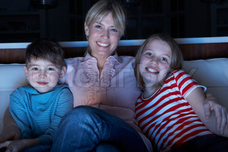 Mother And Children Watching Programme On TV Sitting On Sofa Together