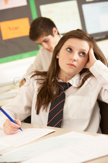 Bored Female Teenage Student Studying In Classroom