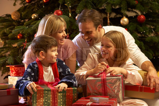 Family Opening Christmas Present In Front Of Tree