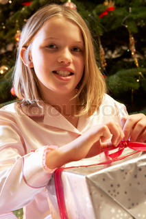 Young Girl Opening Christmas Present In Front Of Tree