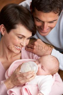 Portrait Of Parents Feeding Newborn Baby At Home