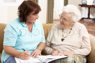 Senior Woman In Discussion With Health Visitor At Home