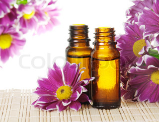 Bottles of Essential Oil and Pink Flowers
