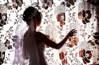 Silhouette of the bride at the window