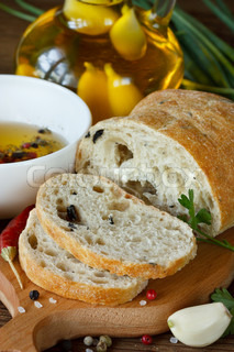 Fresh bread ciabatta and aromatic olive oil with herbs and spices.