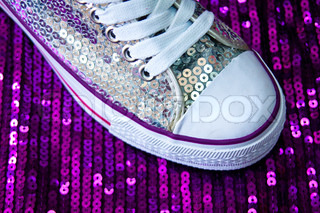 sneakers on a violet sequin background