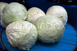 Several cabbage heads placed on a counter in an open marketplace