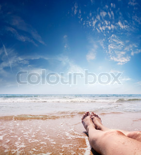 female feet in crystal clear sea water