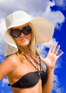 Young beautiful sexy tanned blond woman with hat and bikini laying on sea beach