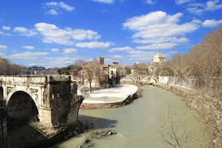 Roman Island Isola Tiberina with a fragment of the ancient bridge over the turbid river Tiber with bright sky