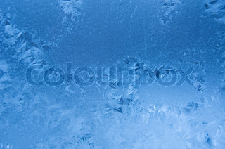 Slightly blurred blue frost pattern on a window glass (as an abstract winter background)