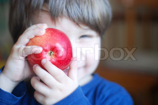 Little smiling boy in blue holding red apple in front of his face