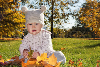 Baby with maple leaf playing in the park