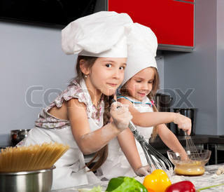 two little girls having fun on the kitchen table with raw food, clothing cooks