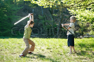 Two boys playing in the green forest.  They are fightinh with plastic swords.