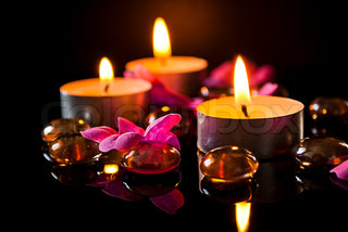 Three candles, petals and stones at black background