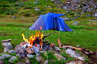 Camping tent and bonfire in the mountains