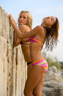 Two young girls pose on a beach