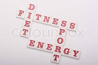 Plastic cubes with letters make crossed words: a diet, sports, fitness and energy.